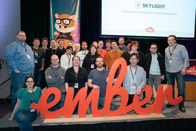 Ember core team members gather around the Ember sign at EmberConf